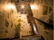 イニヘアデザインワークス(inni hair design works)の雰囲気(サロンへの階段の壁がニュースペーパー)