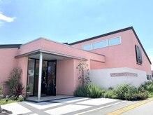 パティオ(PATIO')の雰囲気(ピンク色の外観で隣にヤシの木が立ち並ぶリゾート感をデザイン。)