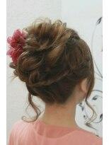 編みこみの編みこみとルーズなシニヨンにピンクのガーベラを添えて画像