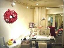 壁にかかった真っ赤なお花のリースがお客様を優しくお迎えします