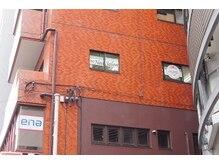 こちらの茶色いビルの3階です。enaの看板の前を右へお入り下さい