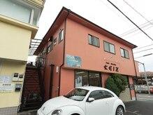 コーラル デュー(Coral dew)の雰囲気(オレンジ色の1階が美容室の建物の2階になります。青い看板が目印)