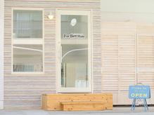 白い建物1階、パステルカラーで優しい色合いの外観です。