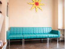 鮮やかなブルー際立つソファーとオーナー手作りの太陽のオブジェ