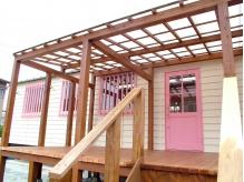 外観。ピンクの扉とウッドデッキが目印です。