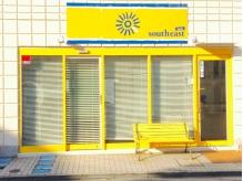 真っ白いブラインドと黄色い看板が目印、入口にベンチがあります