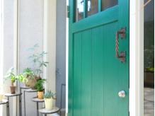 明るい緑色のドアと観葉植物が並んだ、お洒落な外観です♪